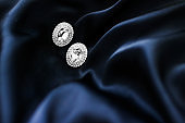 Luxury diamond earrings on dark blue silk background, holiday glamour jewelery present