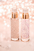 Holiday make-up base gel, serum emulsion, lotion bottle and rose gold glitter, luxury skin and body care cosmetics for beauty brand ads