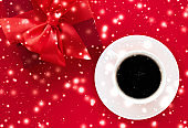Winter holiday gift box, coffee cup and glowing snow on red flatlay background, Christmas time present surprise