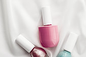 Nail polish bottles on silk background, french manicure products and nailpolish make-up cosmetics for luxury beauty brand and holiday flatlay art design