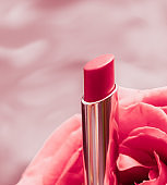Pink lipstick and rose flower on liquid background, waterproof glamour make-up and lip gloss cosmetics product for luxury beauty brand holiday design