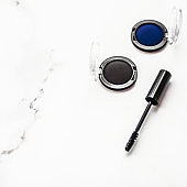 Eyeshadows, black liner and mascara on marble background, eye shadows cosmetics as glamour make-up products for luxury beauty brand, holiday flatlay design
