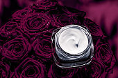 Face cream skin moisturizer and dark purple flowers, luxury skincare cosmetic product on floral background as beauty brand holiday flatlay design