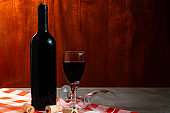 Bottle of red wine in wine cellar for tasting. Red wood background. Wine tradition and culture concept