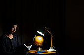 Man sitting in armchair concentrated on reading a book. Dark background with lamp illuminating