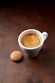 Cup of coffee with amaretti (Italian biscuit) on rustic wooden background.