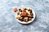 Nuts, raisins and apricots on rustic wooden background. Concept for healthy snack. Copy space.