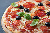 Pizza with chorizo, mozzarella cheese, cherry tomatoes, black olives and oregano. Home made food. Concept for a tasty and hearty meal. Top view. Close up.