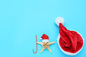 Red santa hats with starfish and candy on blue background