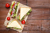 Tasty sandwiches with vegetables on brown wooden table