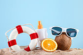 Lifebuoy with sunscreen and fruits on blue background