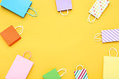 Small paper shopping bags on yellow background
