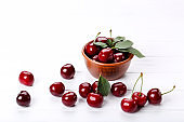 Sweet cherries in bowl on white wooden table