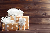 Gift boxes with ribbons on brown wooden table