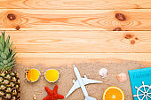 Seashells with fruits, sunglasses and airplane model on brown wooden table