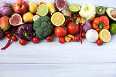 Various fresh vegetables and fruits on a wooden background, top view, copy space.