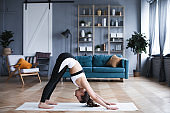 Full length portrait of attractive young woman working out at home, doing yoga or pilates exercise on mat.