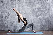 Sporty female practicing yoga in yoga studio.