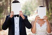 Wedding couple hiding face with blank paper.