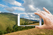 Man hand taking a photo of Zigana Mountain with smartphone in Trabzon, Turkey.