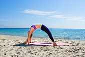 Woman training yoga on the beach. Girl is wearing sportive clothes doing sport on mat on the sea beach.