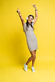 Full length image of pleased woman dancing and listening music while looking at the camera over yellow background.