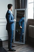 Perfect look. Reflection of handsome young man in full suit adjusting his jacket while standing in front of the mirror indoors.