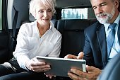 Senior business colleagues working on tablet in back seat of car
