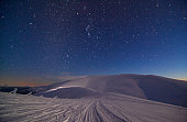 Fantastic starry sky. Winter landscape and snow-capped peaks. Carpathian mountains. Ukraine. Europe.