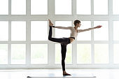 Portrait of attractive happy young woman working out indoors, doing yoga exercise, variation of Natarajasana, Lord of the Dance, King Dancer or Standing Mermaid Pose.