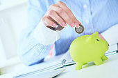 Woman's hand putting money coin in green piggy bank close-up. Growing business, pension and insurance savings concept.
