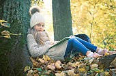 Cute little girl sitting with a book on her lap under the tree in public park. Girl sitting thoughtfully on the ground covered with yellow leaves in the autumn season sunny weather.