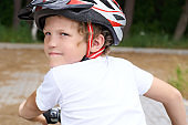 Back view of small boy in protective helmet riding bicycle in park on summer day. Weekend activity.