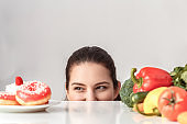 Body Care. Chubby girl standing hiding under kitchen table with vegetables looking at desserts smiling playful close-up