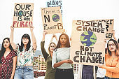 Group of demonstrators on road, young women from different culture and race fight for climate change - Global warming and enviroment concept - Focus on center girls faces