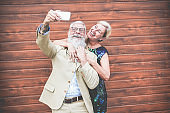 Happy senior couple having fun making selfie story with smartphone - Mature influencers people using new trends technology for social network app - Joyful elderly lifestyle concept - Focus on man face