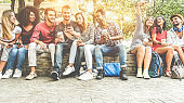 Group of happy friends using smartphones for taking photos and watching videos - Teenagers having fun outdoor with technology trends - Youth and friendship concept - Main focus on center faces