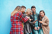 Group of friends watching videos on smartphone - Teenagers addiction to new technology trends - Youth, tech, social, millennial generation and friendship concept - Main focus on center girl face