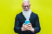 Happy senior man using smartphone app with fluorescent color in background - Hipster old guy having fun with technology - Tech and joyful elderly concept - Focus on his face