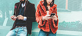 Fashion influencers people using smartphone social media app - Young trendy couple watching story video on mobile cell phone - Technology trends, marketing and new digital job concept - Focus on hands