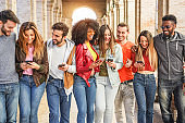 Trendy millennials friends walking together outside of university - Young students having fun laughing and chatting - Youth, lifestyle, friendship and mutiracial concept - Focus on center faces