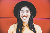 Portrait of happy asian girl smiling with coral background - Young chinese woman having fun posing in front of the camera - Fashion, casual clothes and millennial generation concept - Focus on  face