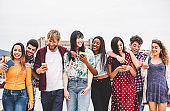 Happy millennials friends walking together outside of university - Young students having fun laughing and chatting - Youth, lifestyle, friendship and mutiracial concept - Focus on faces