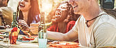 Happy multiracial friends eating, drinking beer and laughing together at barbecue dinner - Young happy people having fun at bbq meal - Friendship and food concept - Focus on right man mouth