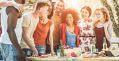 Happy multiracial friends eating, drinking beer and laughing together at barbecue dinner outdoor - Young happy people having fun at bbq meal - Friendship and food concept - Focus on right guys faces