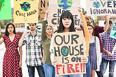 Group of demonstrators on road, young people from different culture and race fight for climate change - Global warming and enviroment concept - Main focus on asian girl face