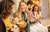 Happy friends eating street food outdoor - Young trendy people having fun together drinking and laughing around downtown streets - City lifestyle and party concept - Focus on blond girl face