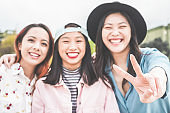 Asian young women friends having fun outdoor - Happy trendy girls laughing together - Millennial generation, bonding, friendship and gathering concept - Focus on hand with peace symbol