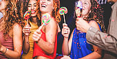 Young friends drinking champagne while dancing inside disco club - Happy people having fun eating candy lollipops at night party - Holidays and nightlife concept - Focus on red hair woman face