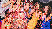 Young friends having party throwing confetti - Young people celebrating on weekend night - Entertainment, fun, new year's eve, nightlife, holidays, concept - Focus on close-up man hands